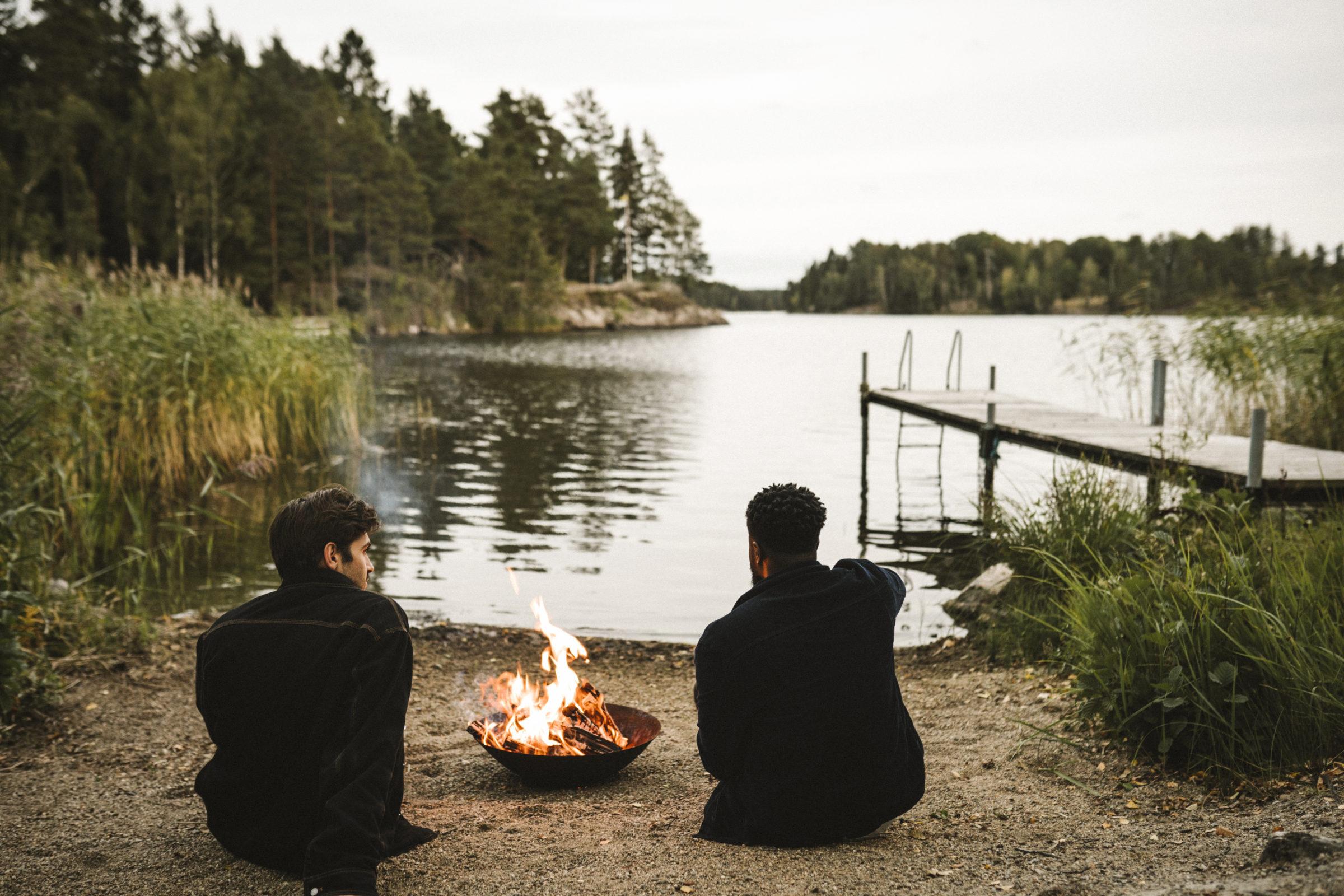 Två personer vid en lägereld vid en sjö.